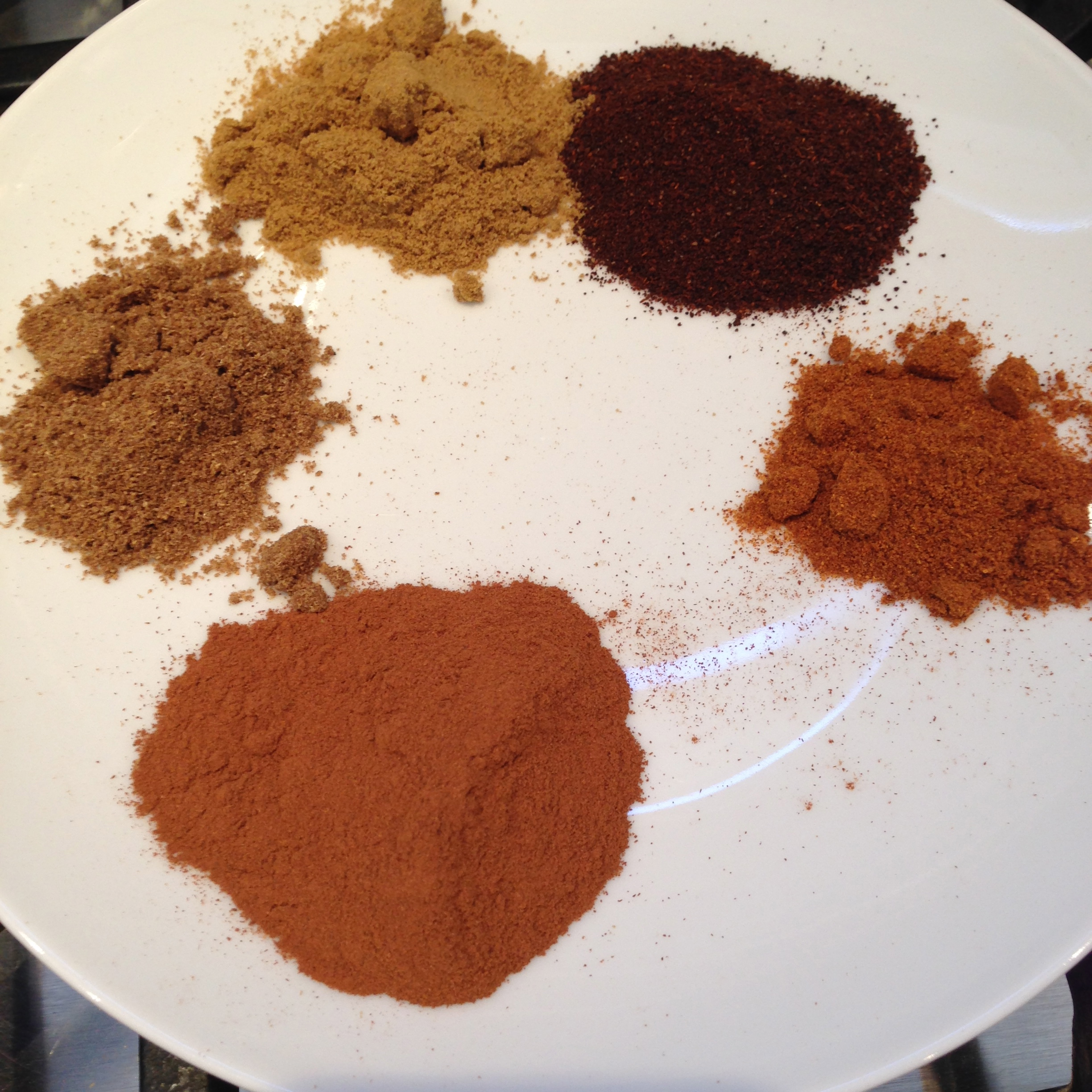 Clockwise: chili powder, cayenne, cinnamon, ground coriander and cumin.